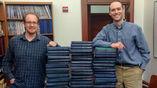 """Джонатан Пэйн (справа) и Ноэль Хейм рядом со стопками """"Трактата о палеонтологии беспозвоночных"""", который они использовали для поиска доказательств закона Копа"""