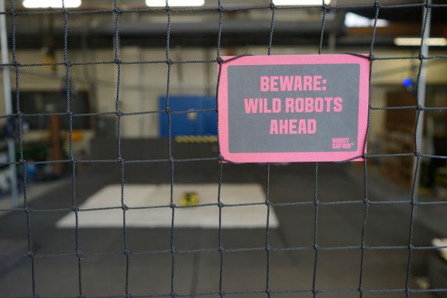 """Надпись: """"Осторожно: впереди дикие роботы"""""""