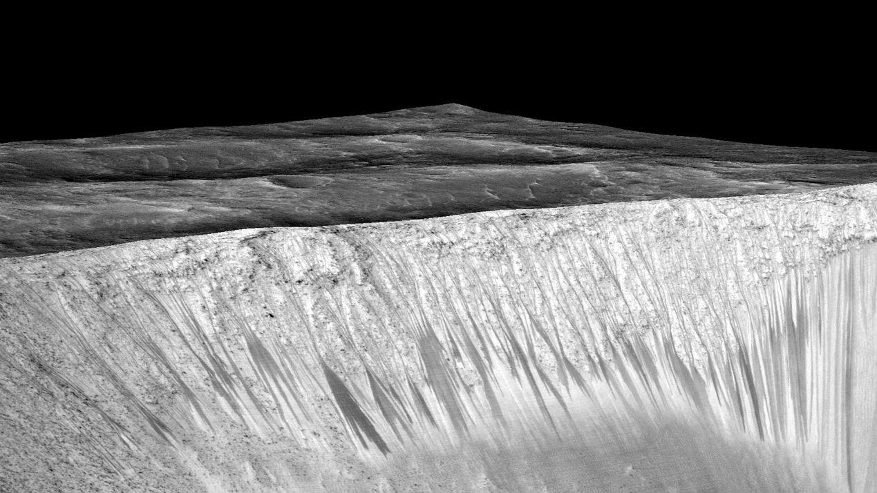 Учёные называют такие тёмные полосы recurring slope lineae. Здесь показаны полосы кратера Гарни на Марсе. Длина каждой полосы порядка нескольких сотен метров. Теперь учёные считают, что они сформированы водой