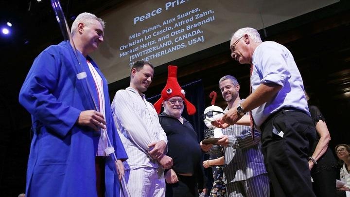 Слева направо: Алекс Суарес, Кристиан Ло Кашо, Маркус Хайц, Мило Пухан. Заслуженную статуэтку учёные получили из рук нобелевского лауреата Оливера Харта.
