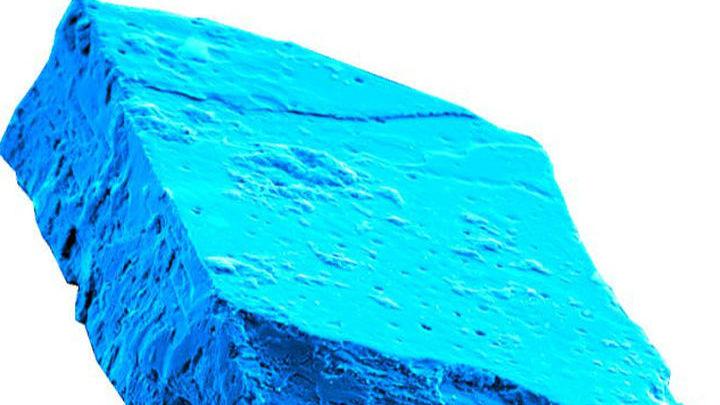Кристаллы хибонита под микроскопом имеют характерный голубой цвет.
