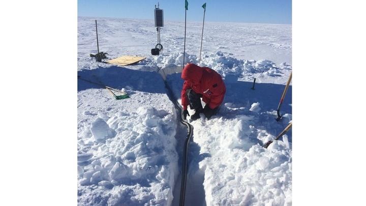 Учёные закладывают в снежный покров систему, которая будет питать высокочувствительные сейсмометры.