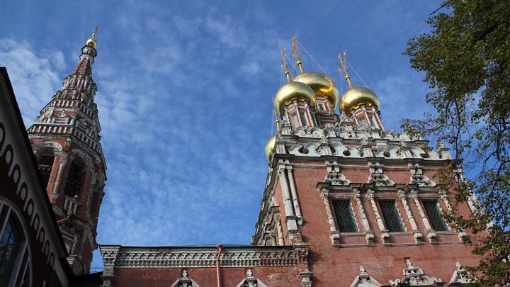 Архитектурное убранство старинной церкви Воскресения в Кадашах в стиле московского барокко с белокаменным декором и остатками солнечных часов на фасаде.